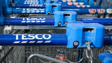 Shopping trolleys are pictured outside a Tesco supermarket in north London, on August 29, 2014. British supermarket giant Tesco on Friday issued another profits warning and slashed its shareholder dividend by 75 percent, blaming challenging trade and high investment costs. AFP PHOTO/Leon Neal